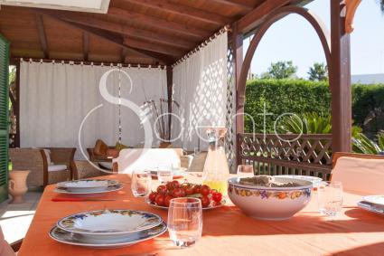 La veranda ombreggiata è arredata con sala pranzo e divanetti relax