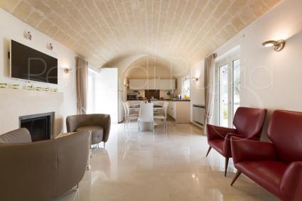 L`open space con soggiorno e angolo relax, e in fondo sala da pranzo e cucina a vista